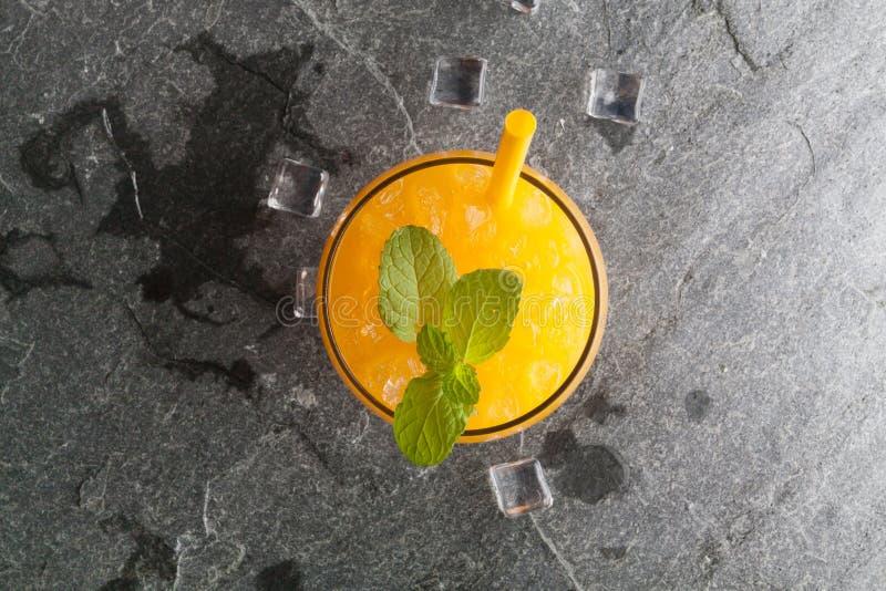 Orangen und Saft auf Steintischplatteansicht lizenzfreie stockfotografie