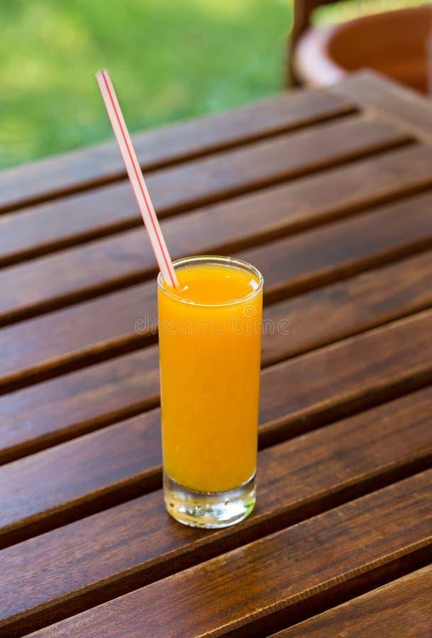 Orangensaft auf hölzernem Tabellenhintergrund Saft auf einem grünen Hintergrund draußen lizenzfreie stockbilder