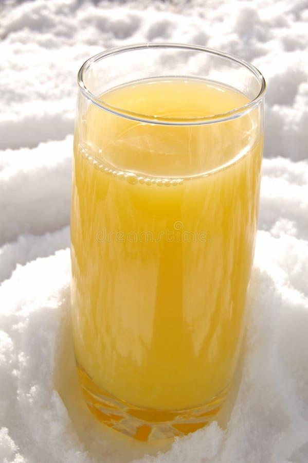 Orangensaft auf Schnee lizenzfreie stockfotografie