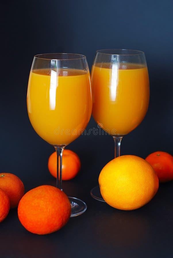 Orangensaft in den Gläsern mit Zitrusfrüchten auf dunkelblauem Hintergrund Vertikales Bild lizenzfreie stockbilder