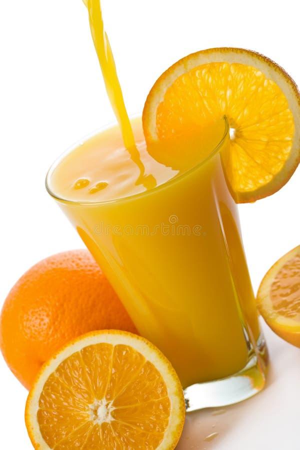 Orangensaft, der in das Glas getrennt gießt lizenzfreie stockfotografie