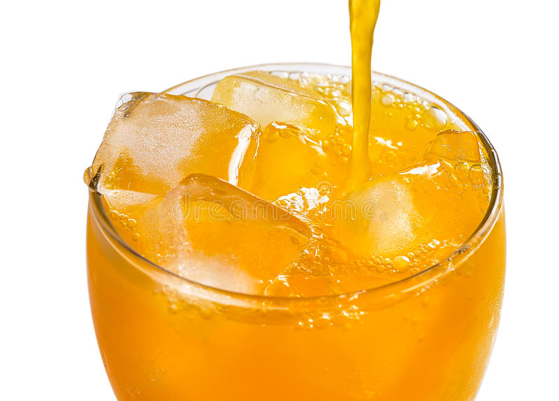 Orangensaft, der in Glas gießt lizenzfreie stockbilder