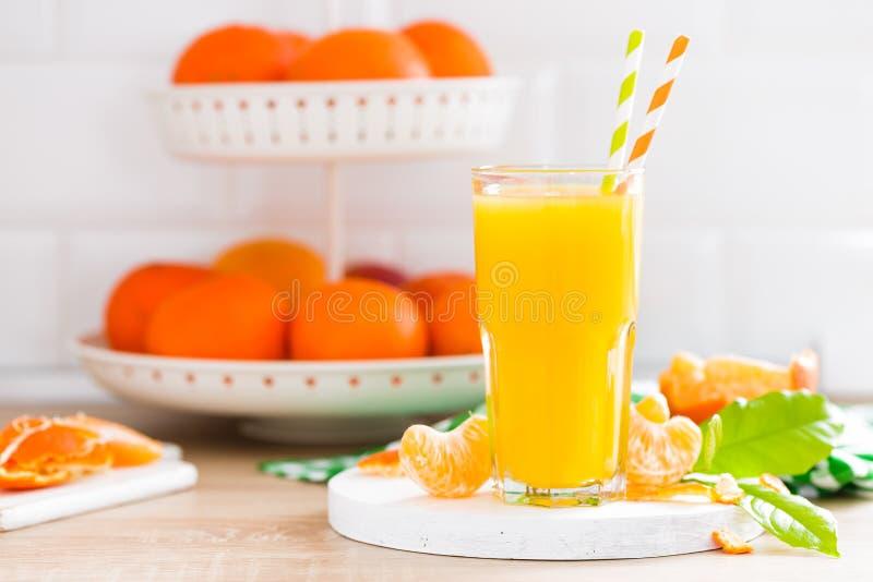 Orangensaft der Tangerine in den Glas- und frischen Früchten mit Blättern auf weißer hölzerner Küchenhintergrundnahaufnahme Gesun lizenzfreie stockbilder