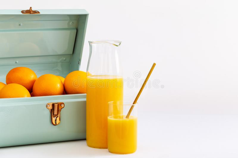 Orangensaft in einem Glas und in einem Krug durch einen blaues Metallkleinen Koffer voll Orangen über einem weißen Hintergrund stockbild