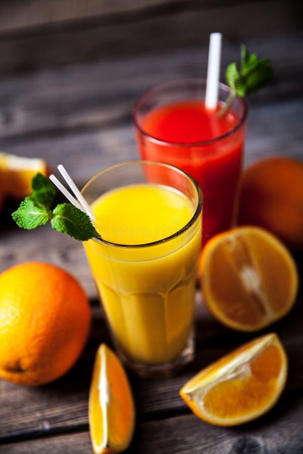 Orangensaft im Glas mit Minze, frische Früchte auf hölzernem Hintergrund a stockbilder