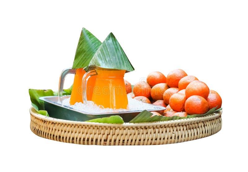 Orangensaft im Klarglasglas witih Bananenblatt, im Eis und in der Mandarinefrucht auf dem hölzernen gesponnenen Behälter lokalisi lizenzfreies stockbild