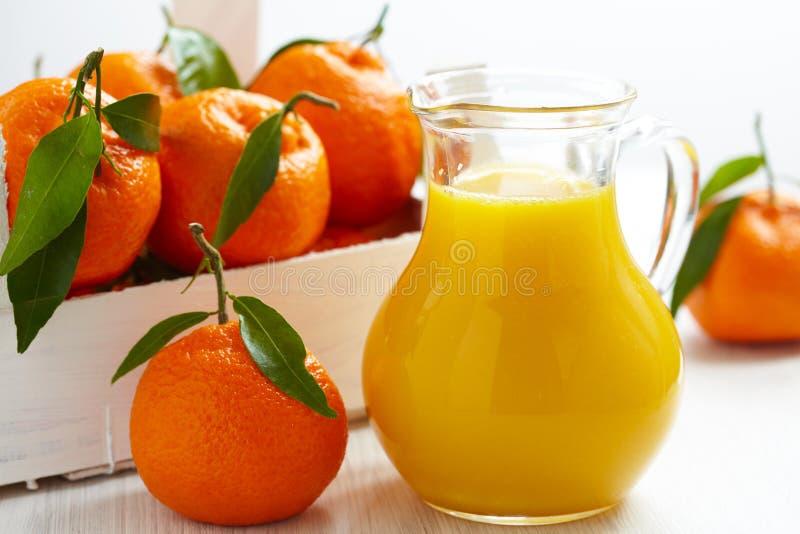 Orangensaft im Krug und in den Tangerinen lizenzfreie stockfotografie
