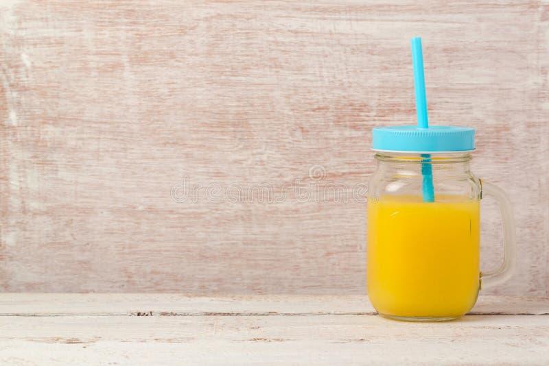 Orangensaft im Weckglas über hölzernem Hintergrund mit Kopienraum Gesunde Ernährung oder Nähren stockfoto