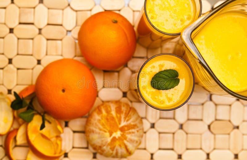 Orangensaft mit Gläsern lizenzfreie stockbilder