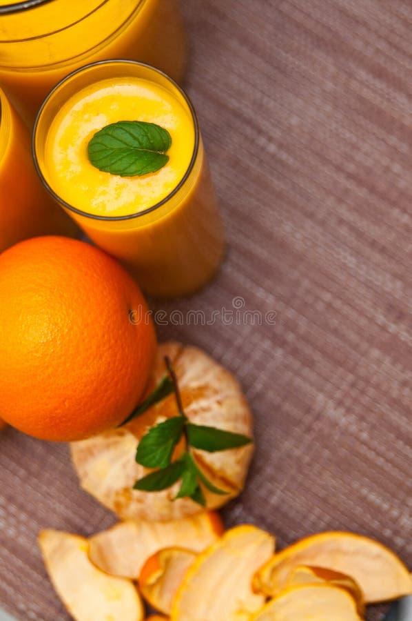 Orangensaft mit Gläsern stockbilder