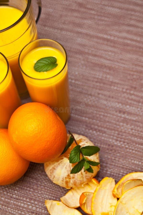 Orangensaft mit Gläsern lizenzfreie stockfotos