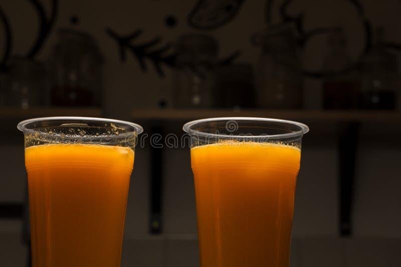 Orangensaft in zwei Plastiktrinkgläsern, gesunder Getränkhintergrund mit Kopienraum Das verpackte neue Getränk, das zu bereit ist stockfoto