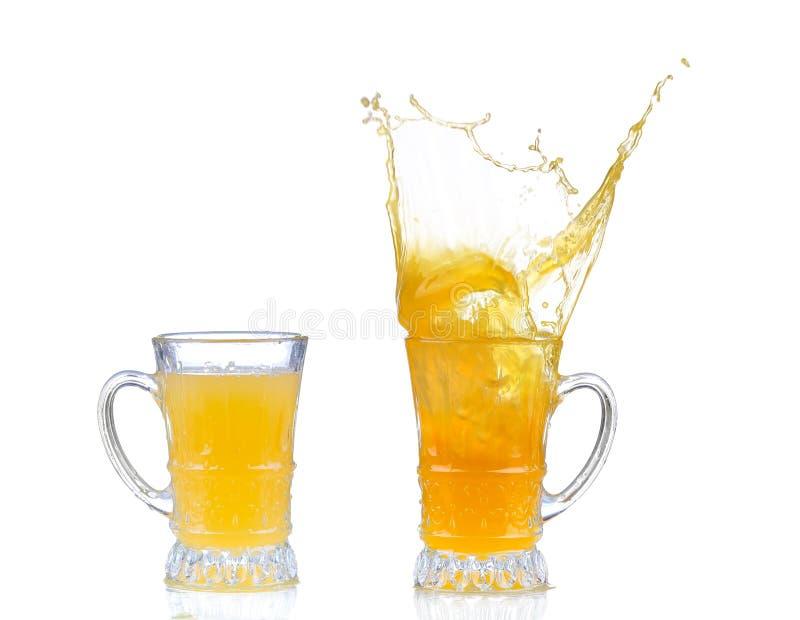Orangensaftspritzen im Glas lokalisiert auf Wei? lizenzfreie stockfotos