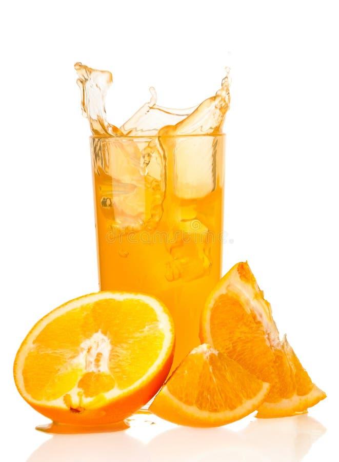 Orangensaftspritzen im Glas und in den Scheiben der Orange auf weißem backg stockbild