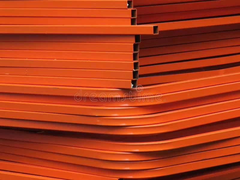Orangery: stacked ornage colored metal fences. A huge stack of orange stacked colored metal frames or fences royalty free stock photo