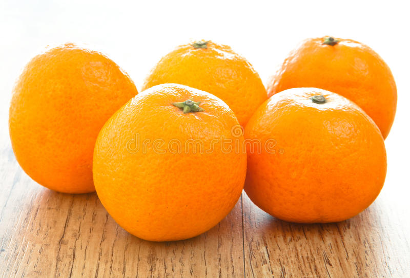 Oranges. Fresh oranges on a wooden surface royalty free stock photo