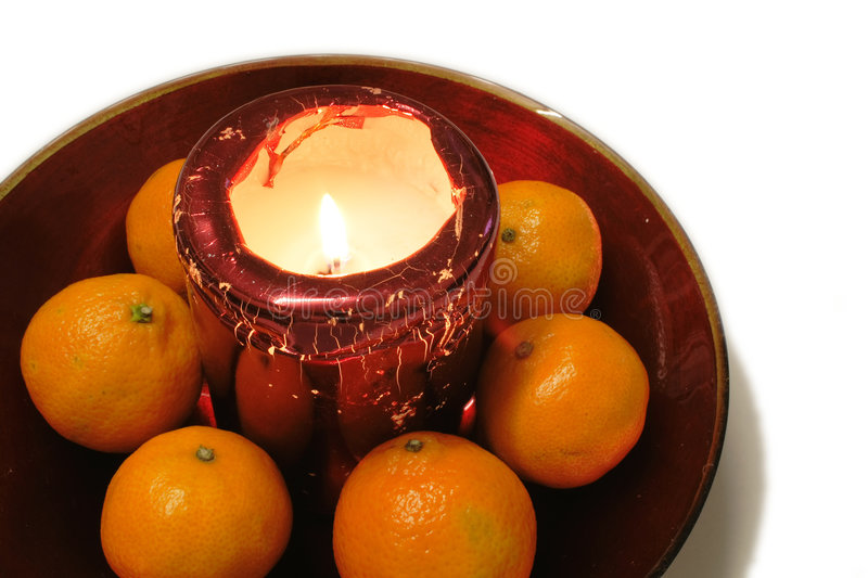 Oranges around a christmas candle decoration royalty free stock images
