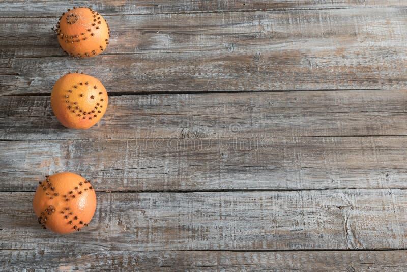 Oranges avec l'épice de clou de girofle sur la vieille table en bois images stock
