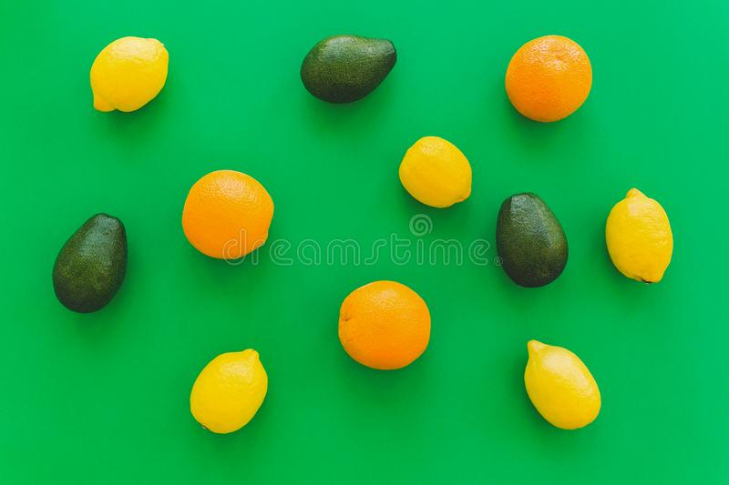 oranges, avocado and lemons on bright green paper trendy background, flat lay. modern summer image concept. multi fruit flat stock images