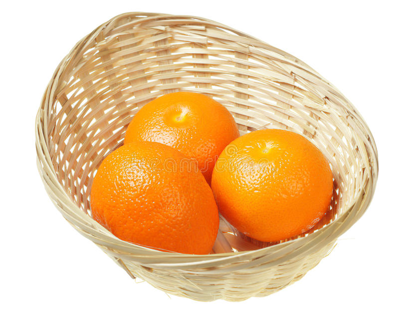 Oranges in a basket. Three fresh oranges in a wicker basket, isolated royalty free stock photos