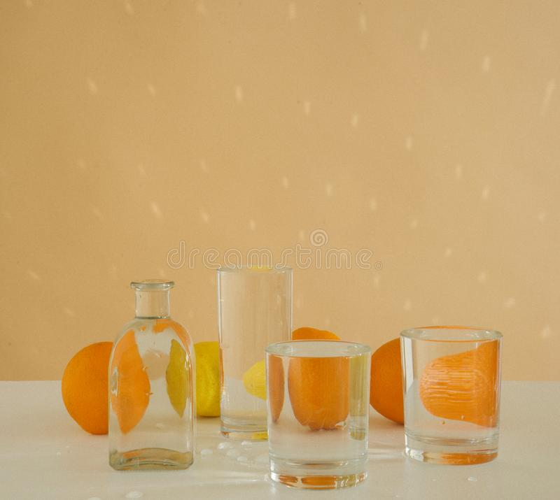 Oranges behind glass vessels filled with water. Distorted reflection on a beige background royalty free stock photos