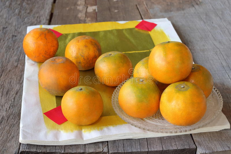 Oranges with Chinese traditional paper on old wooden board background. Happy Chinese new year concept. stock photos