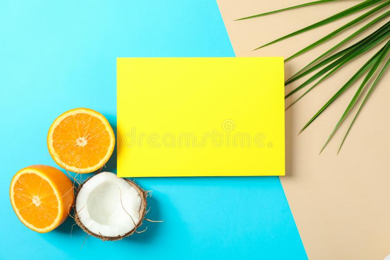 Oranges, coconut, palm leaves and square with space for text on two tone background. Summer vacation royalty free stock photo