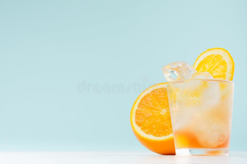 Oranges cold alcohol drink with liquor layers, sliced orange, ice cubes in misted shot glass on pastel blue background. stock images