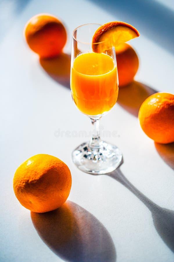 Oranges colorées vives fraîches sur une table blanche et un verre de fre image libre de droits