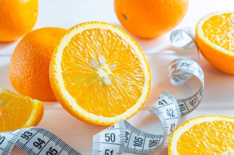 Oranges coupées en tranches et entières, et bande de mesure fraîche sur la table en bois blanche images libres de droits