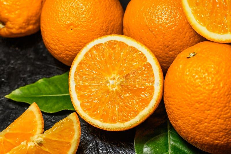 Oranges coup?es en tranches et enti?res sur le fond fonc? photo libre de droits