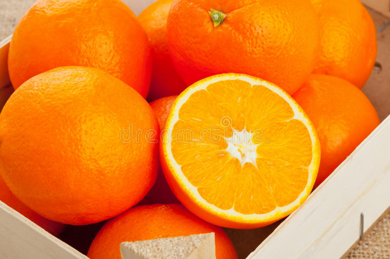 Oranges crate. Whole and cut organic oranges in wooden crate royalty free stock photography