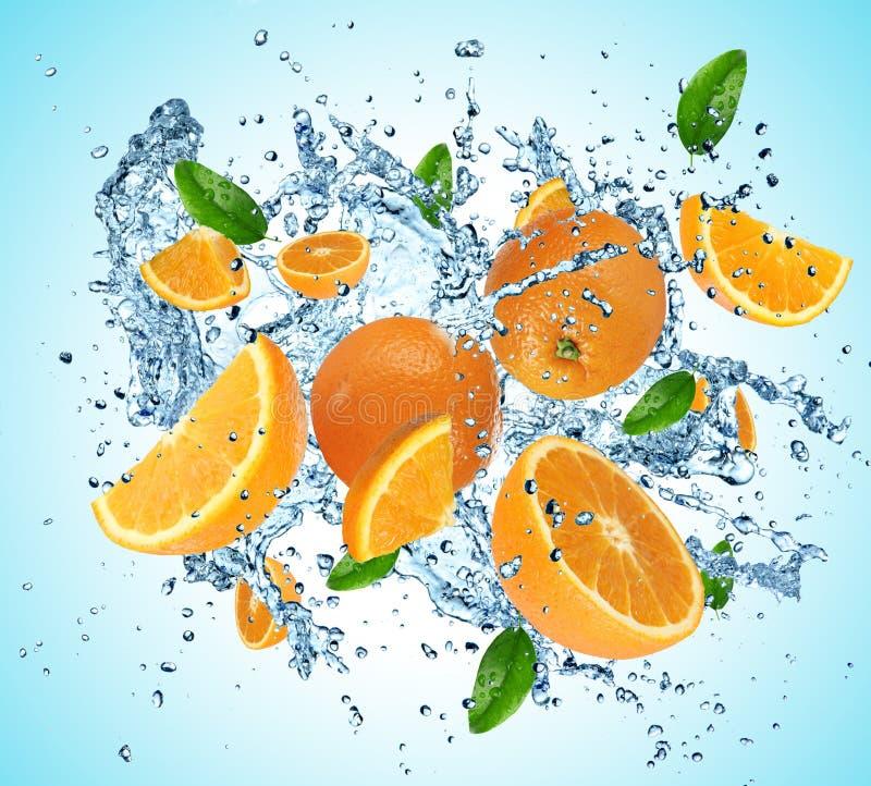 Oranges dans l'éclaboussure de l'eau photographie stock libre de droits