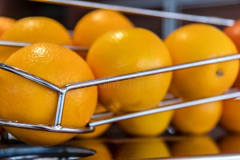 Oranges dans la ligne sur la machine de jus photographie stock