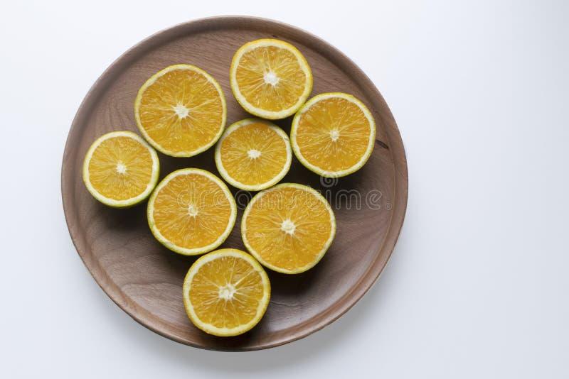 oranges dans les moitiés d'un plat en bois image libre de droits