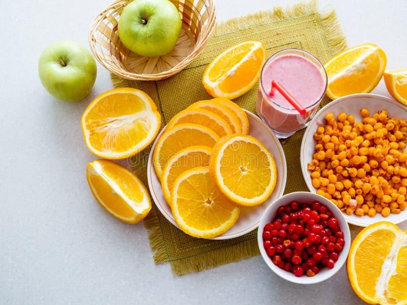 Oranges et cocktail juteux coupés en tranches de baie sur la table Vue de ci-avant images stock