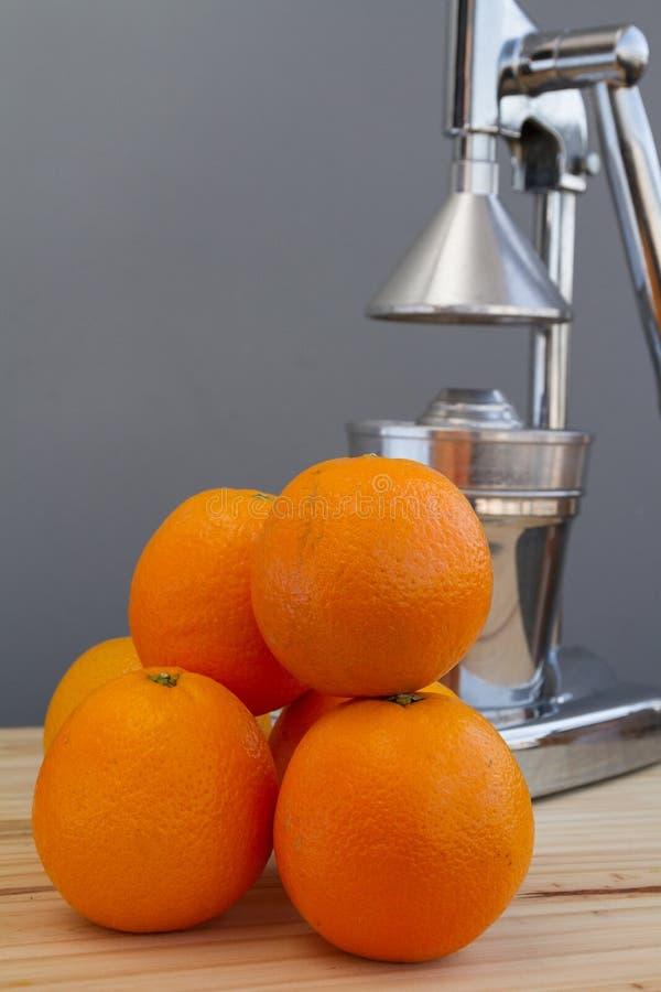 Oranges et presse-fruits d'agrume de chrome photographie stock libre de droits
