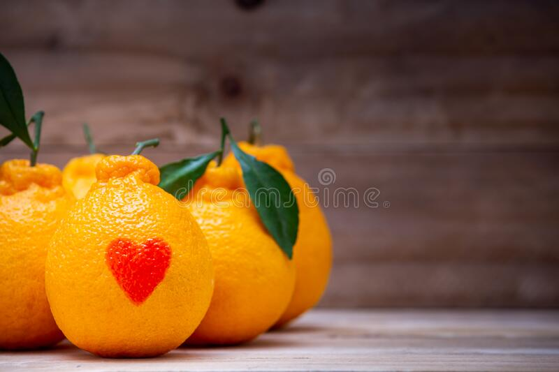 Oranges have a red heart-shaped put on the wooden table stock photography