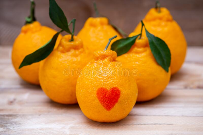 Oranges have a red heart-shaped put on the wooden table royalty free stock photos
