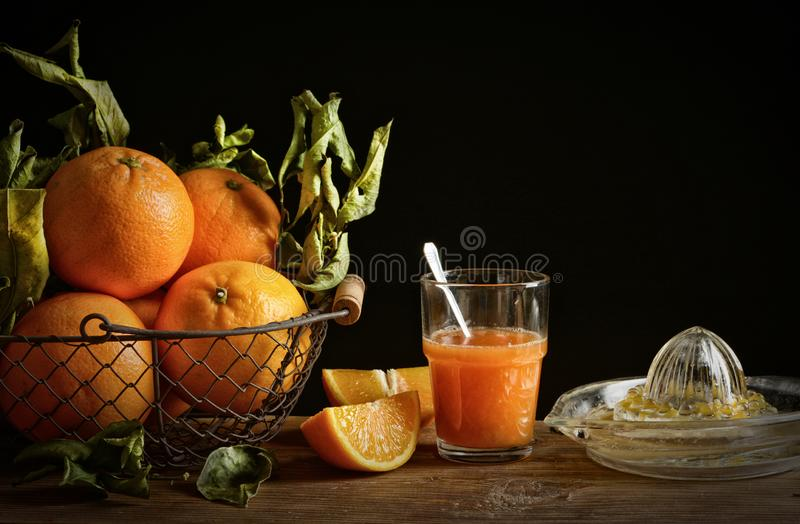 Oranges juice on wooden table with black background royalty free stock photo