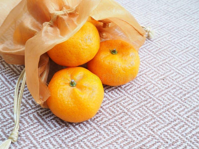 Oranges laissées tomber du sac en soie d'or photo stock