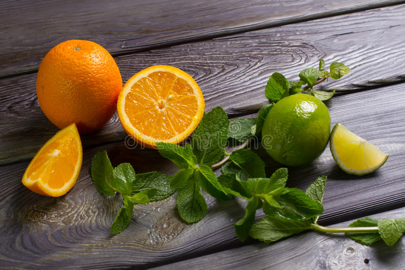 Oranges with lime. Oranges with lime and fresh mint on wooden board stock photography