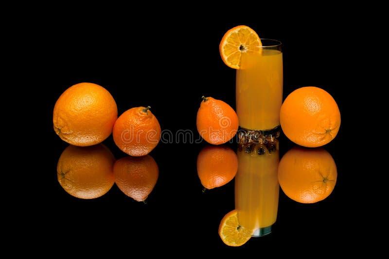 Oranges, mandarines et jus sur un fond noir photographie stock libre de droits
