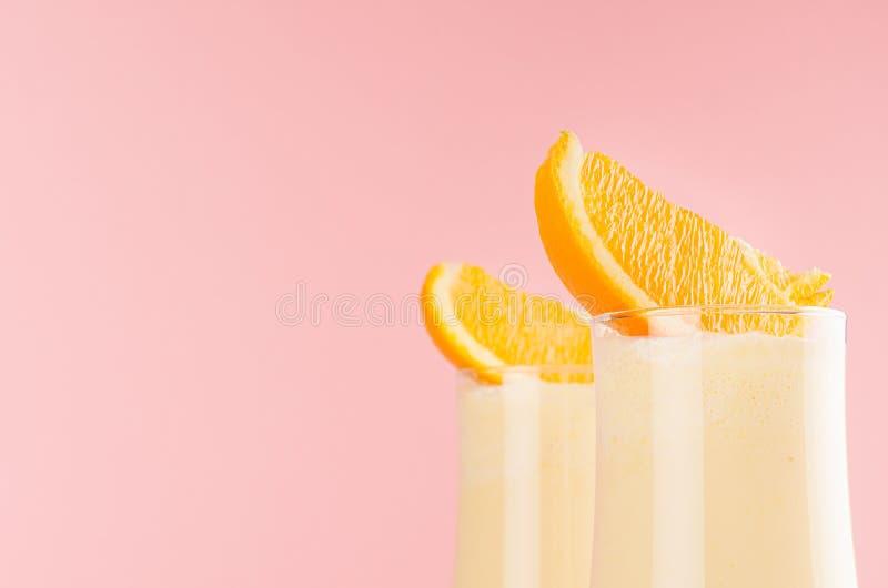 Oranges milkshake with sweet pieces oranges macro, details, top section on soft light pastel pink color, copy space. Oranges milkshake with sweet pieces oranges royalty free stock photo