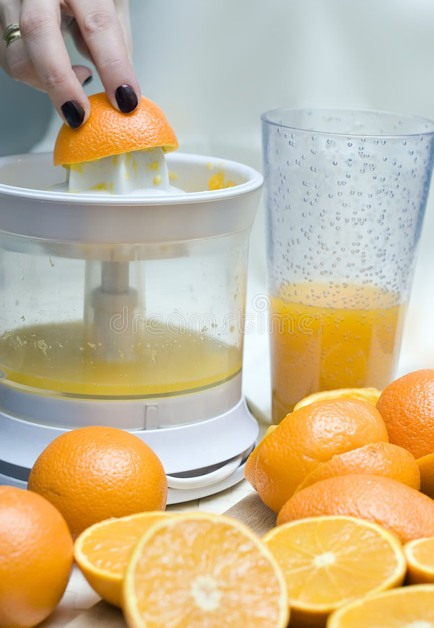 Oranges and mixer. A chopping board covered with oranges, mixer (blender) and a glass with orange juice in the background. A woman's hand pushing the fruit royalty free stock photography