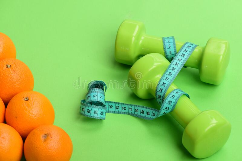 Oranges near dumbbells, cyan measuring tape on green background stock photography