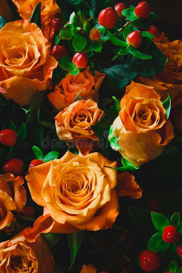 Oranges and orange roses on wooden table stock photography