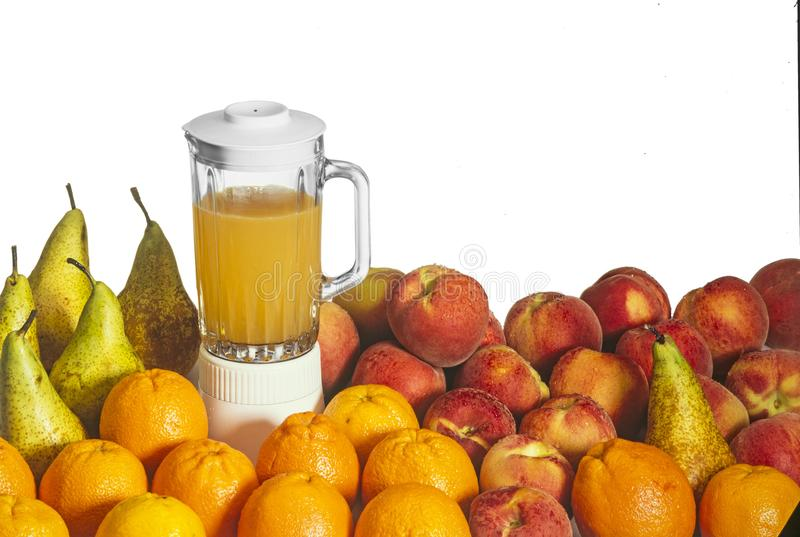 Oranges, peaches, pears and juice in a blender royalty free stock photography