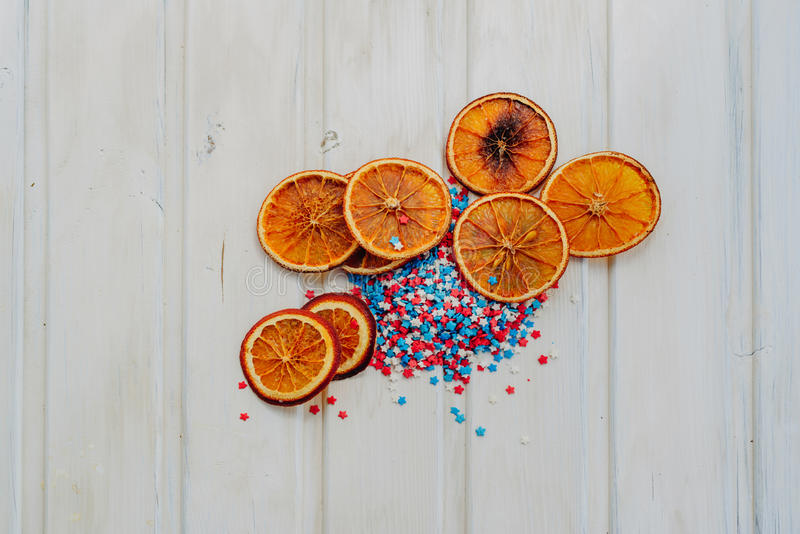 Oranges and stars. Slices of dried oranges and star sprinkles on a white background with copyspace stock images