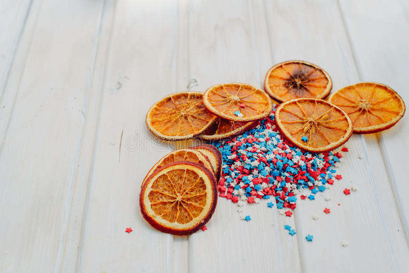 Oranges and stars. Slices of dried oranges and star sprinkles on a white background with copyspace royalty free stock photography